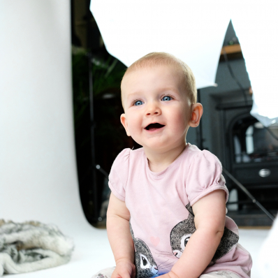 photo shoot of a cute baby with big blue eyes in front of studio lights