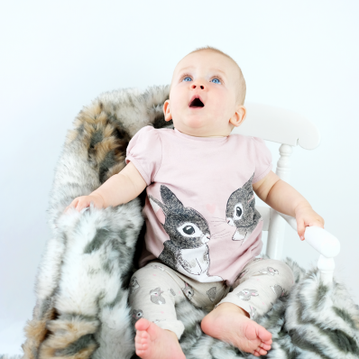 photo shoot of a cute baby with big blue eyes crawling on a fur rug