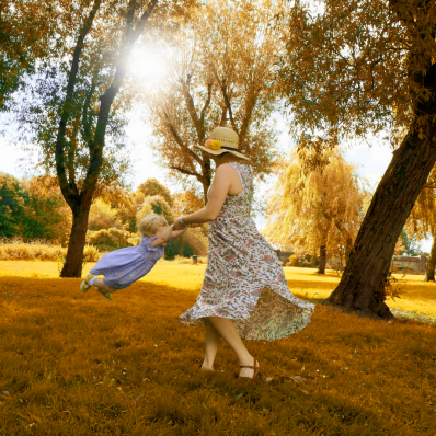 mother and daughter playing in a sunny field in birmingham