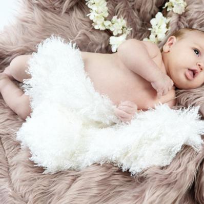 Cute baby lying on a fluffy rug
