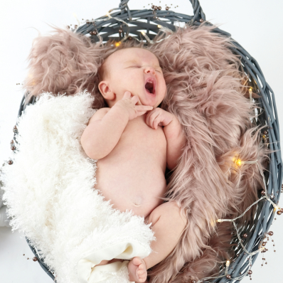 yawning baby in a basket