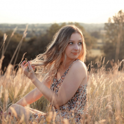 girl playing with her hair in a sunset field in redditch worcestershire