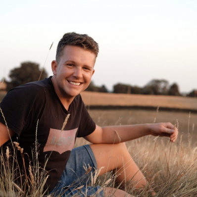 Boy smiling in the grass in a sunset field in redditch worcestershire