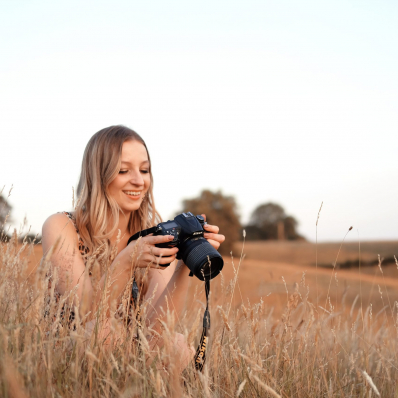 girl with a camera in a sunset field in redditch worcestershire
