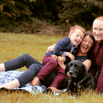 family laughing on picnic blanket at morton stanley park redditch
