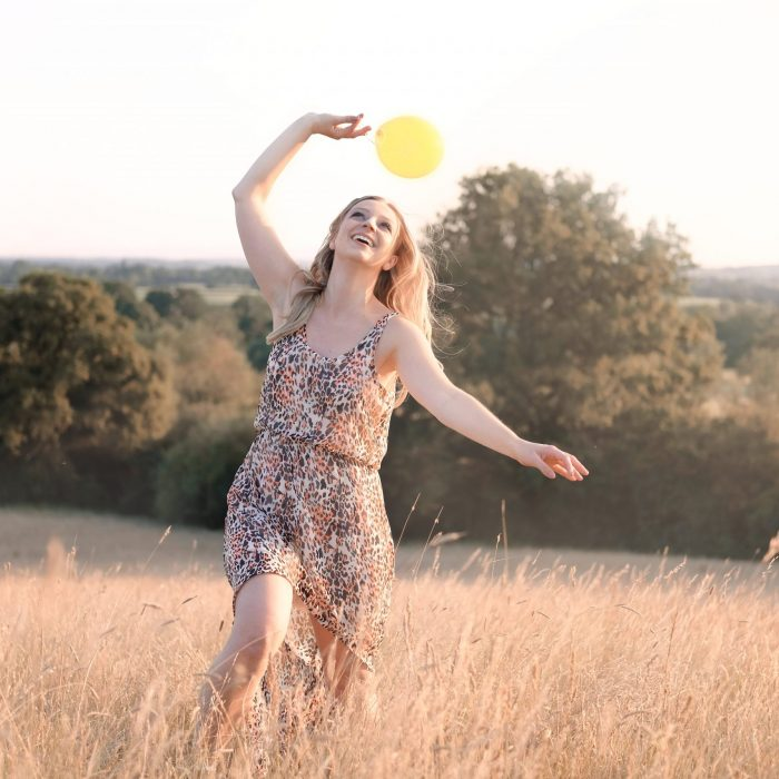 girl playing with a yellow balloon in a sunset field in redditch worcestershire